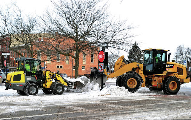 Mike Ullery | Daily Call Piqua street crews use heavy loaders to remove snow from the downtown area on Tuesday morning. Significant snow fall over the past two weekends forced officials to haul some of the accumulation away in order that motorists may park in downtown Piqua.