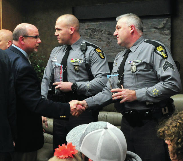 "Piqua City Schools superintendent Dwayne Thompson sakes the hand of Ohio State Highway Patrol Sgt. Dave Rosbison during a special award presentation at Thursday's school board meeting. Robison, along with Troopers Jason Hutchison, Charlges ""Chip"" Gannon, and Tim Davis were recognized for their efforts in saving the lives of a pair of Piqua City Schools employees following a bus crash on I-75 in December of last year."
