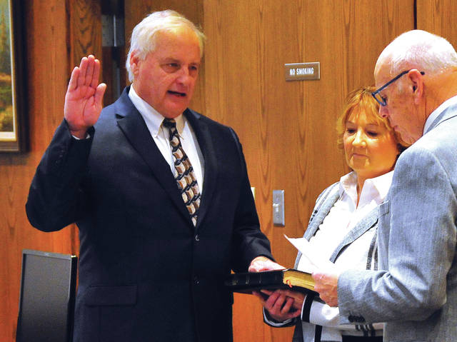 Mike Ullery | Miami Valley Today Ted Mercer, left, takes the oath of office as Miami County Commissioner in commission chambers at the Miami County Safety Building on Thursday.