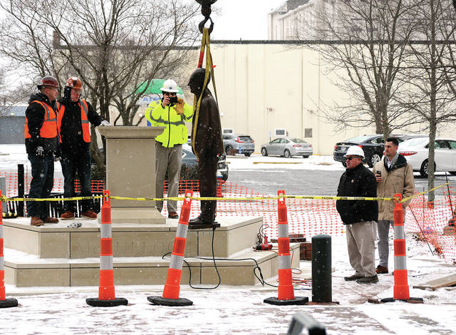 Piqua city officials and workers from Piqua Steel prepare to hoist the statue of William McCulloch onto its pedestal on McCulloch Square on Thursday morning.