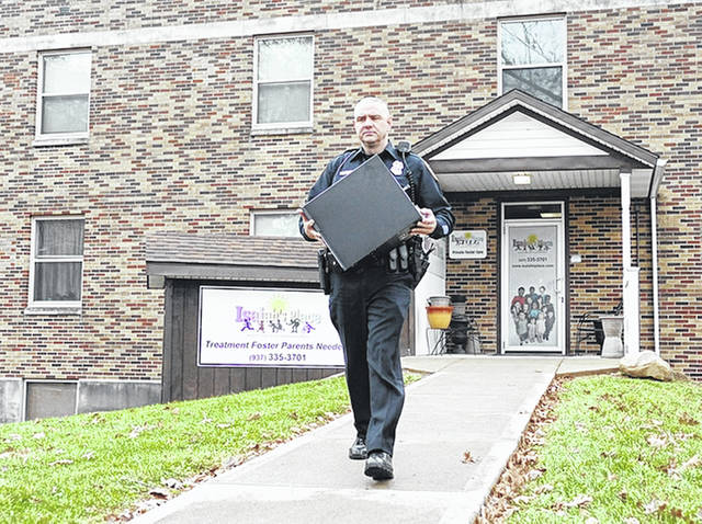 Officers from the Troy Police Department remove items during a search warrant at the office of Isaiah's Place, a suite inside the Stouder Center, on Nov. 23, 2016, in Troy.