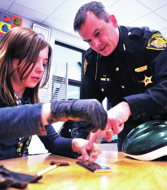 Miami East fifth grader Kaci Manns gets some advice on lifting fingerprints from her father, Miami County Sheriff's Deputy Richard Manns, during a Crime Scene Investigation class at Miami East Elementary School on Monday.