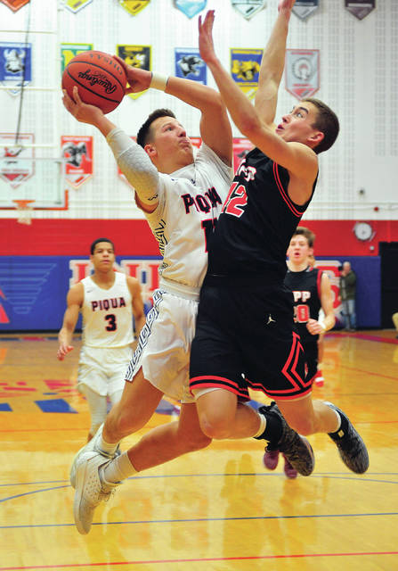 Piqua's Mick Karn puts up a shot as Tippecanoe's Grifffin Caldwell defends Friday night at Garbry Gymnasium.