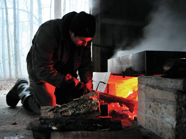 Miami County Park District volunteer Chip Gade keeps the fire hot as he boils sap at sunup on Thursday at Maple Ridge Reserve. The park district will be boiling sap again on Sunday.