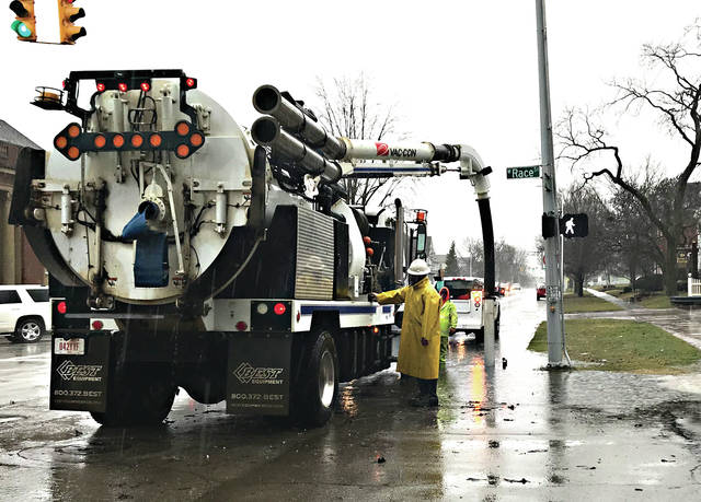 Mike Ullery | Miami Valley Today City of Troy sanitation workers pump water and debris from a storm sewer on South Market St. at Race St. during Thursdays heavy rain. Recent heavy rains combined with melting snow were more than storm sewers and the already saturated ground could take, leading to widespread standing water and flooding.