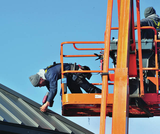 Mike Ullery | Miami Valley Today Workers from Harlow Builders in Troy brave brisk temperatures on Tuesday as they work on the roof at Sherwood Shopping Center.