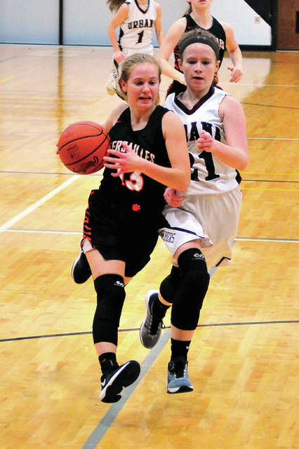 Versailles' Caitlin McEldowney races down the floor in front of Urbana's Marissa Horn Thursday at Covington.