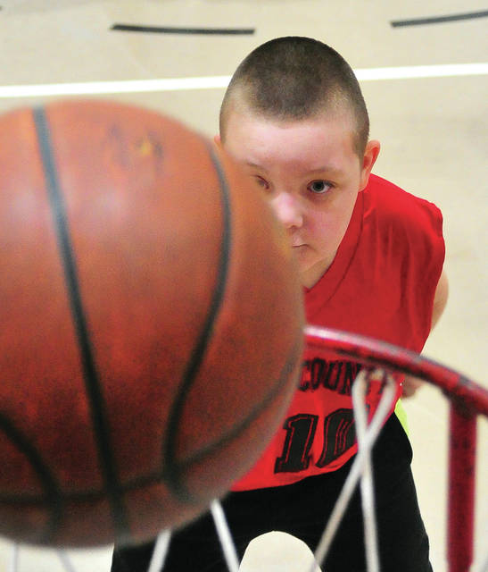 Mike Ullery | Miami Valley Today Joseph Eply, 8, of Troy watches his shot fall through the hoop, scoring two points for his Miami County Magic basketball team, during a game on Friday against the Upper Valley Career Center IM class.