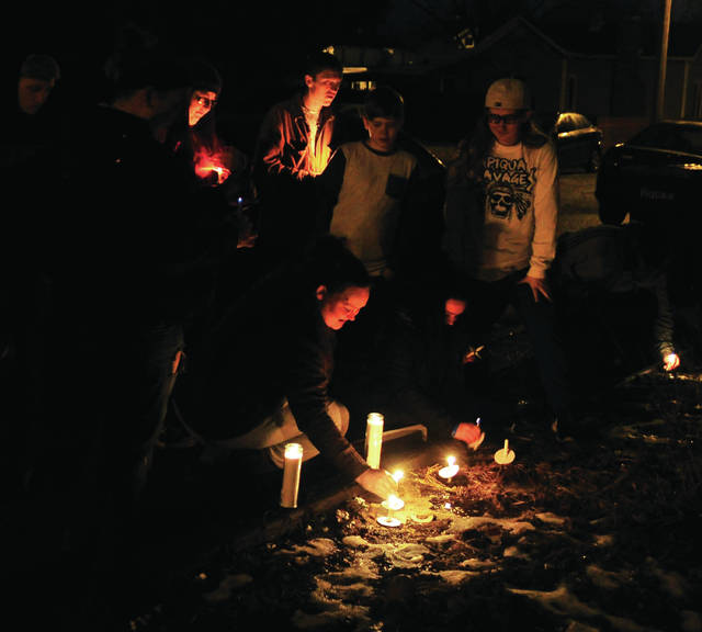 Mike Ullery | Miami Valley Today Friends and relatives of Mickey S. Cole, 43, who was found dead on a sidewalk on Cherry Street in Piqua on Friday morning hold a candlelight vigil Saturday evening at the spot where Cole's body was discovered.