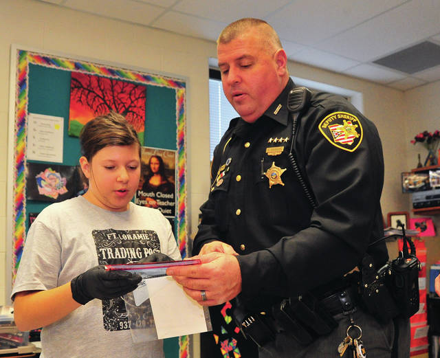 Deputy Roger Davidson of the Miami County Sheriff's Office works with Abby Maxson, a sixth-grader, at Miami East during a CSI class recently at the school.