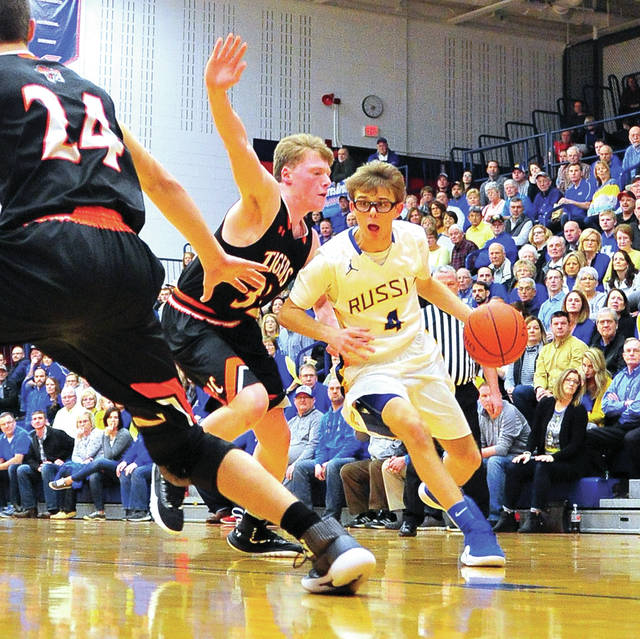 Russia's Mason Dapore drives to the basket as Jackson Center's Aiden Reichert defends Saturday night at Garbry Gymnasium.