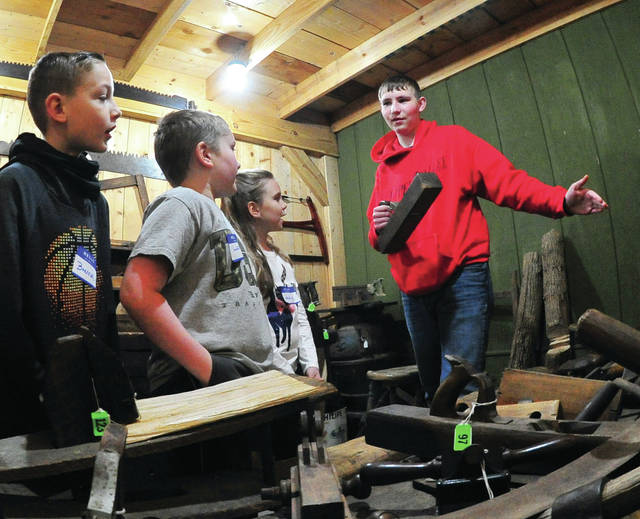 Hunter Evans of Covington, an Environmental Occupations student at Upper Valley Career Center, explains had tools that were used during the 19th century to third grade students from Washington Primary School during a tour of the Garbry Museum at Willowbrook on Tuesday morning.