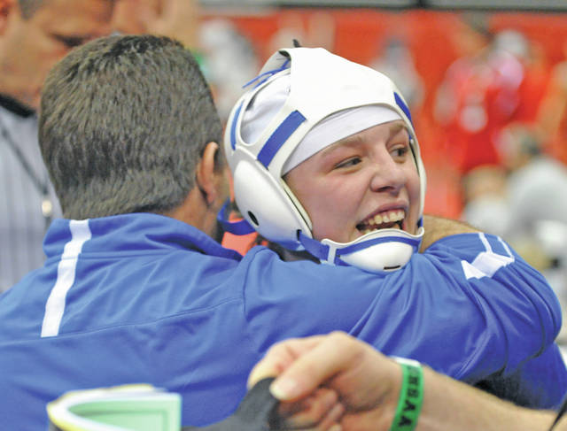 Josh Brown|Miami Valley Today Miami East's Olivia Shore is embraced by Viking assistant coach Rich Randall after winning her first-round match at the Division III state wrestling tournament Thursday at the Schottenstein Center. Shore, only the second girl ever to qualify for the tournament, became the first to ever win a first-round match.