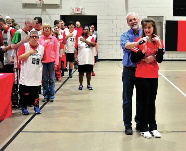Miami County Magic cheerleader Haley Cerbus, right, performs the National Anthem prior to Friday's Spirit Night basketball game at Riverside School A large crowd turned out toe watch the Magic in their 2018-2019 season finale.