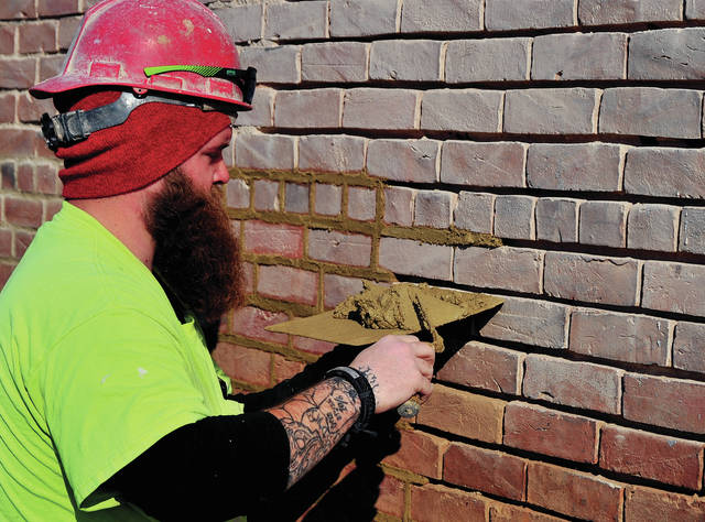 Mike Ullery | Miami Valley Today Nick Goodin of Quality Masonry in Marion, Ohio, works on tuck pointing brick at the old Mo's South Seas Lounge building on South Main Street in Piqua on Tuesday. The renovation of the building is part of the city's Riverfront landscape project.
