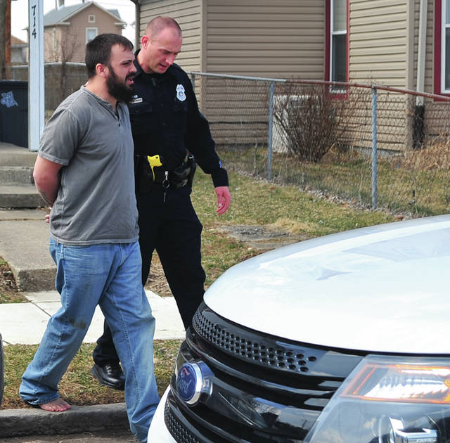 Mike Ullery | Miami Valley Today A Troy police officer takes Alexander Blair into custody near his South Crawford Street residence on Tuesday following an alleged incident in Butler Township.