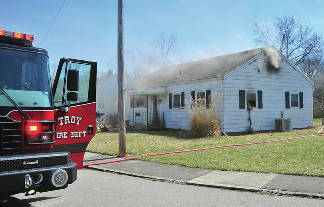 Mike Ullery | Miami Valley Today Firefighters from Troy battle a house fire on Mayfair Circle on Wednesday afternoon.