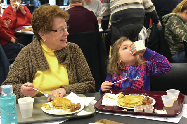 Cody Willoughby | AIM Media Midwest Marjorie and Evelyn Stilwell, of Piqua, enjoy breakfast together during the second annual Kiwanis Club Pancake Day and Flapjack 5K on Saturday at Upper Valley Career Center. The breakfast was open to the public, with all-you-can-eat pancakes, sausage, and applesauce available. Race participants were offered a free breakfast upon registration. All proceeds benefitted the youth of Piqua.