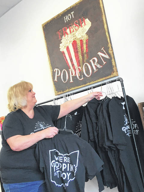 Cody Willoughby | AIM Media Midwest Liz Smith, co-proprietor of Poppin' Off Popcorn, hangs T-shirts available for purchase ahead of the store's Friday opening. The new location will offer custom popcorn, ice cream, craft sodas, and more.