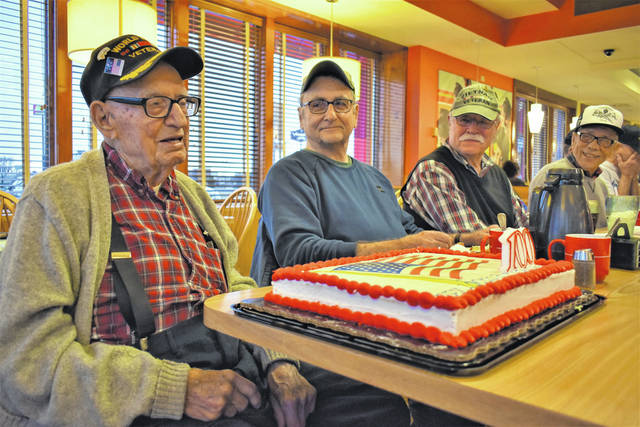 Cody Willoughby | AIM Media Midwest John H. Teeters, far left, is presented a 100th birthday cake by fellow veterans during a monthly breakfast at Frisch's Big Boy. Teeters will turn 100 years old on Tuesday, March 26.