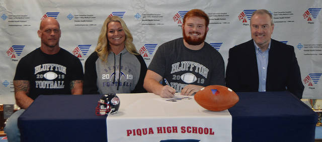 Rob Kiser|Call Photo Piqua High School senior Caden Clark signed his letter of intent to play football for Bluffton University Wednesday as his parents look on. From left to right are Chad and Brandy Lawson, Clark and Chris Clark.