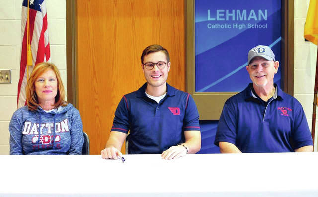 Mike Ullery|Call Photo Lehman Catholic senior Michael Denning signed his letter of intent to play football for the University of Dayton Friday in the LCHS Media Center. Shown with Denning are his mom Gail and dad Rick.