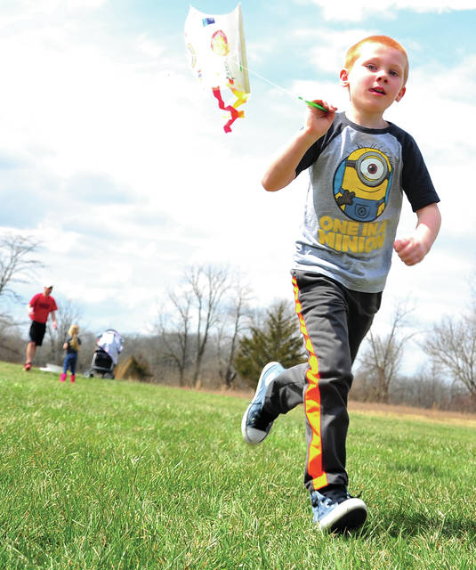 Abram Wysocki, 5, of Troy races to get his kite aloft at the Miami County Park District Stillwater prairie on Saturday. during the VIP Kreature Kite Fly event.