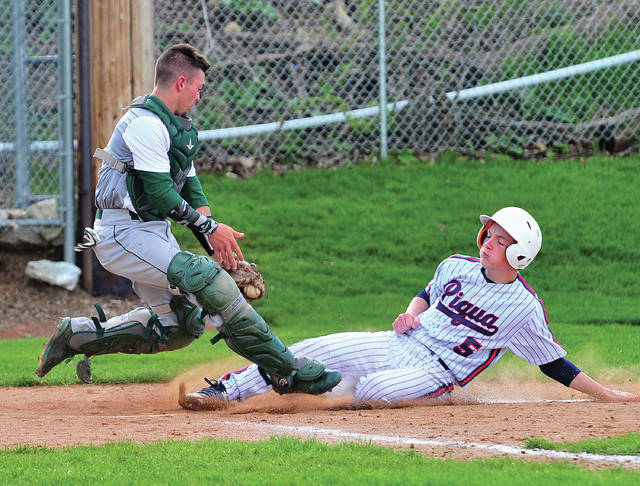 Piqua's Zack Lavey slides in ahead of Greenville catcher Ethan Saylor's tag Tuesday at Hardman Field.