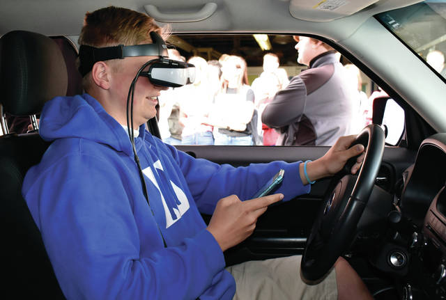 "James Horne, a junior at Miami East High School, attempts to text while ""driving"" an impaired driving simulator during Wednesday's Arrive Alive event at the high school."