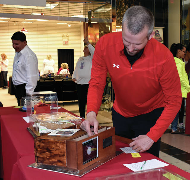 """Andrew Snyder, Recruiting Coordinator at Upper Valley Career Center, """"powers up"""" the school's Cakes For A Cause entry on Thursday evening at the Miami Valley Centre Mall. The cake, designed by UVCC Pre-Engineering students, with the cake baking done by Culinary Arts students, actually plays Mills Brothers music. Bidding on cakes in this annual Piqua Community Foundation event will take place on Friday from noon until closing. Bids may be placed in person at the mall or may be called in at 937-778-3422. The auction will be broadcase live on WPTW/Muzzy Broadcasting at 1570 AM and 98.1 FM. The auction will be live-streamed at98.1 WPTW. More than 70 cakes have been donated for this year's event. ©2019 Miami Valley Today"""