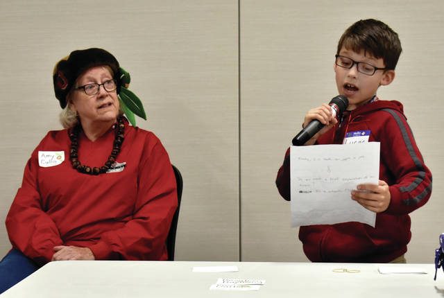 Lucas Bahun, 9, a third-grade student at Troy Christian School talks about how trees help the environment as Amy Cullis from Troy's Beautification Committee and Arbor Day Chairperson, looks on during Friday's Troy Arbor Day event. Due to rain, the event was moved to the Bravo Room at Hobart Arena. This year's event was dedicated to the late Dr. Thomas Redick, a long-time Troy resident and council member. Although the event was held indoors, the City of Troy planted a Buckeye tree at Menke Park. Mayor Mike Beamish announced at the ceremony that the City of Troy has earned the designation Tree City USA for the 33rd consecutive year. © 2019 Miami Valley Today