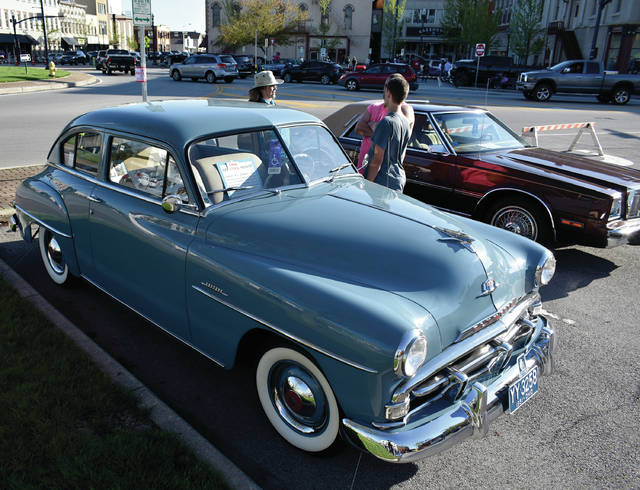 Karen Purke, Damien Price, and Robert Adkins, all of Troy, chat about cars in front of Nick Essinger's 1951 Plymouth Concord during Friday's Downtown Troy Car Show. © 2019 Miami Valley Today