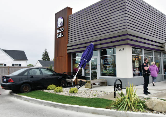 A car rests against the Taco Bell building on Covington Avenue in Piqua on Tuesday morning after the young driver lost control, went through a fence and table while attempting to drive through the parking lot. The driver was not injured and damage to the Taco Bell building was minimal. ©2019 Miami Valley Today