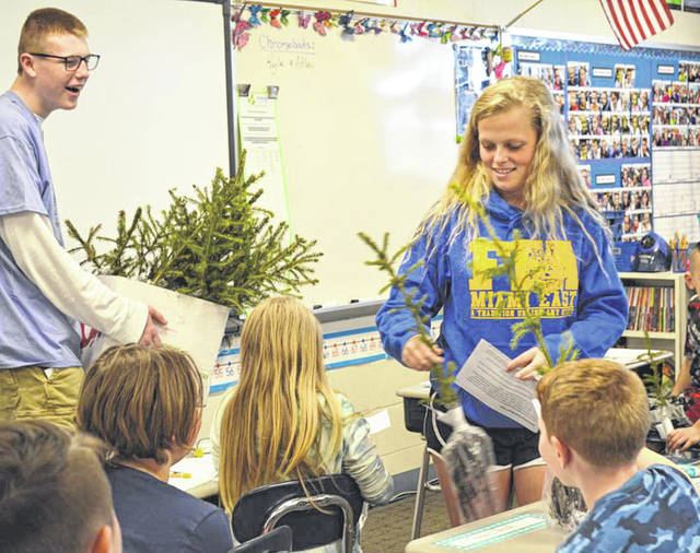 Provided photo Adam Bensman, left, and Morgan Nosker distribute trees to fourth graders at Miami East Elementary School.