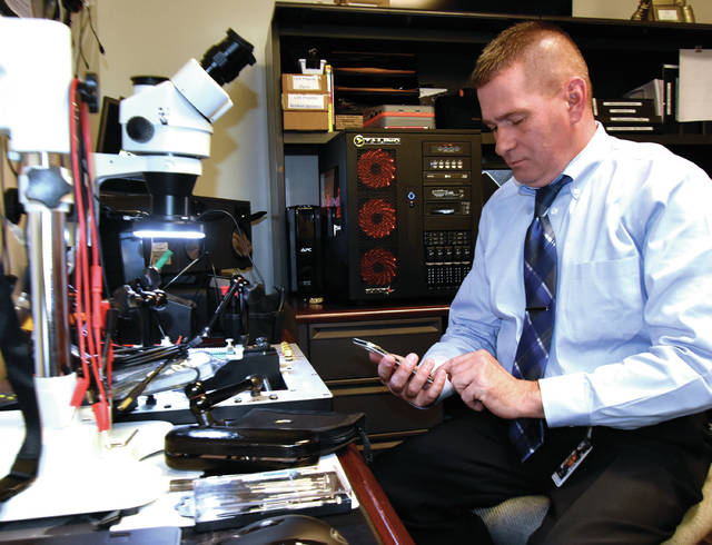 Detective Todd Cooper of the Miami County Sheriff's Office demonstrates some of the equipment acquired by the sheriffs office to extract data from cell phones and computers. All of the computers and other tools were provided, at no cost to the county, by the United States Secret Service upon Cooper's completion of schooling to become proficient in computer and cell phone forensics.