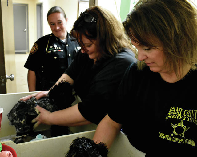 Deputy Sarah Fraley watches as volunteers Laura Seger and Kelly Moore bathe two of the puppies that were rescued from an alleged puppy mill on Peebles Road, near Troy, on Monday.