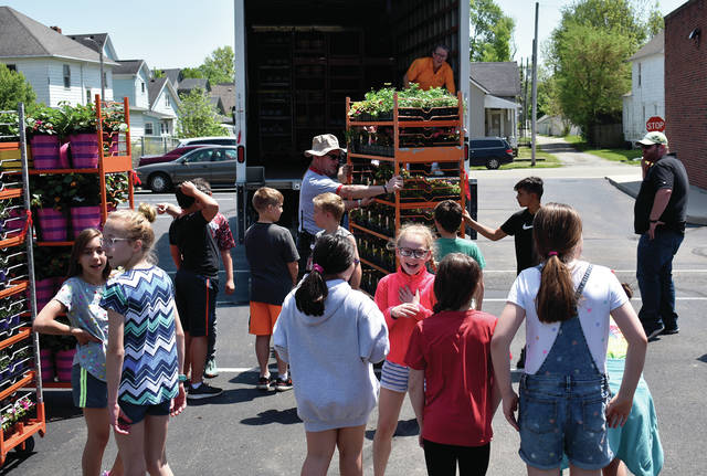 Students and staff at Forest Elementary School unload hundreds of flower in the parking lot on Wednesday afternoon in preparation for the annual Spring Flower Sale pick-up and Family Night at the school. ©2019 Miami Valley Today, All rights reserved