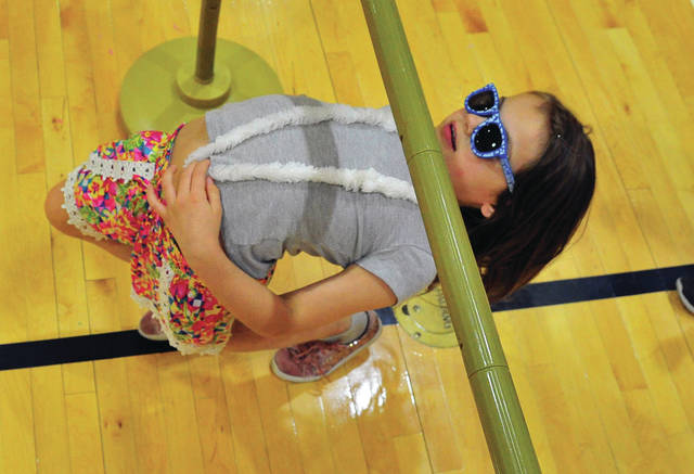 Lauren Pergram, a first-grader at Washington Primary School, demonstrates her limbo dance skills during Thursday's Attend-Dance Luau. More than 330 of Washington's students earned an invitation by missing less than four days of classes during second semester. Also participating in the Attend-Dance were more than 225 students from Springcreek Primary School. The event was sponsored in part by a generous donation from AT&T ©2019 Miami Valley Today, All rights reserved