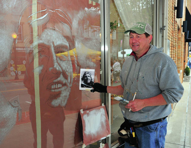 Artist Michael Glass of Greenville checks his original photo as he paints Piqua native, World War II hero, and National Aviation Hall of Fame enshrinee Don Gentile on a downtown storefront window during Friday's Taste of the Arts event.