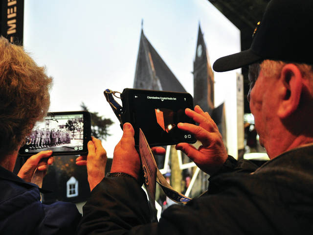 Russ Martin, right, and his wife Mary, of Grove City, are among the first visitors to the National Museum of the United States Air Force to tour the newly-opened D-Day 75th Anniversary display at the museum The augmented reality display, the first of its kind in the United States, takes visitors on a virtual tour of one of the D-Day landing zones in Normandy. Guests can rent hand-held devices and follow paratroopers from their exiting their Troy, Ohio-built WACO gliders and C-47s to the very spot where they landed behind the lines.The display opened on Monday and will be open through the end of this year. ©2019 Miami Valley Today