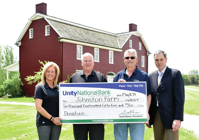 Julie Monnin and Scott Rasor of Unity National Bank present a donation check for $6,454 to Andy Hite and Mike Gutmann from the John Johnston Farm & Indian Agency on Thursday. ©2019 Miami Valley Today, All rights reserved
