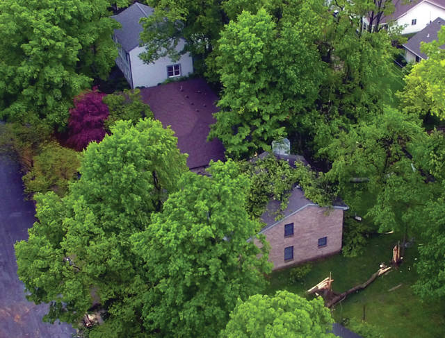 A large tree rests on the roof of a Tipp City home after a lone of severe storms passed through the area early Friday morning.