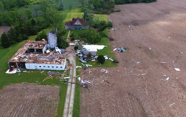 A large barn and silo in the 3000 block of South Rangeline Road lies scattered about after being hit by Monday's tornado.