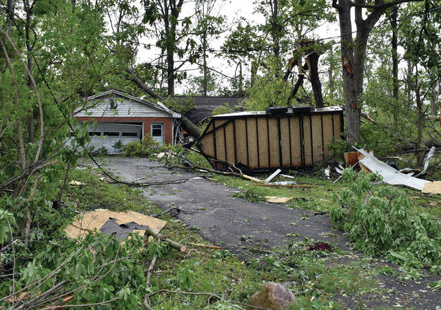 A mobile home trailer lays on its side in front of a heavily damaged Union Townships home.