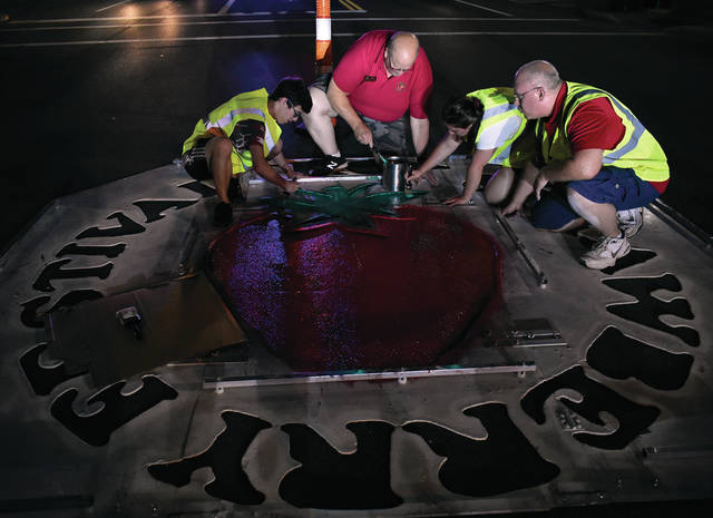 Troy Strawberry Festival chairman for 2019, Bruce Adamson, second from left, along with former festival chairman Matt Watkins, far right, Conner Watkins, 15, and Jaclyn Watkins, 19, paint the traditional Troy Strawberry Festival logo in downtown Troy on Tuesday evening. The festival kicks off on Saturday. ©2019 Miami Valley Today, All rights reserved