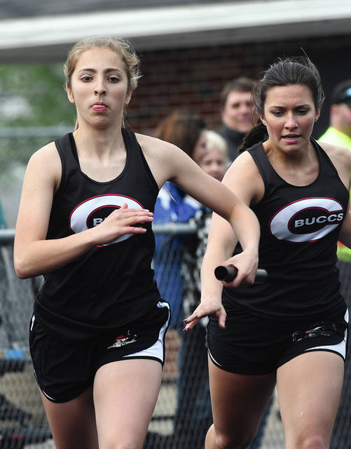 Ben Robinson|GoBuccs.com Covington's Alyssa Kimmel takes a handoff from Maci White in the 800-meter relay Friday at the Covington Invitational.
