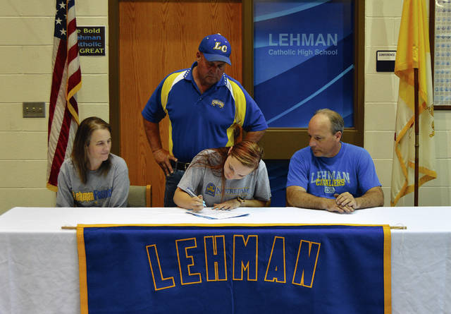 Rob Kiser|Miami Valley Today Lehman Catholic graduate Madalyn Kirtley signs her letter of intent to play softball for Notre Dame College. In front are her mother Jodi and father Benjamin. In back is Lehman Catholic softball coach Bill Booth.