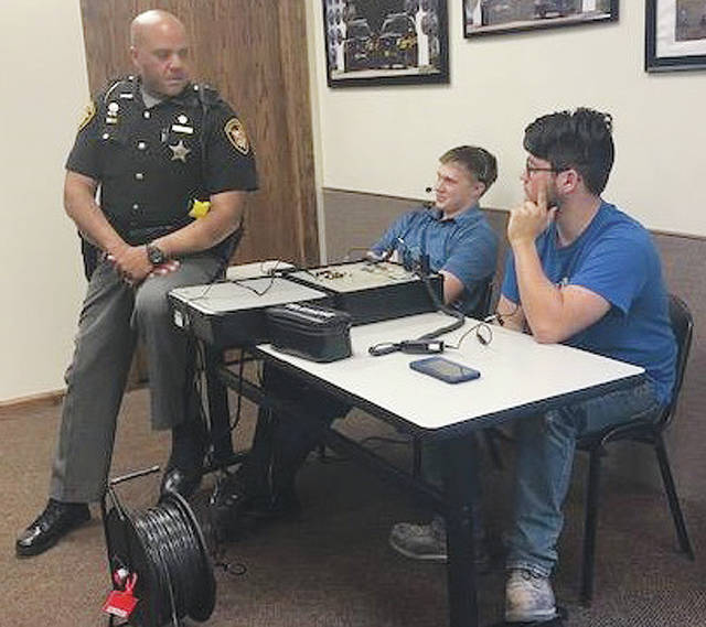 Deputy Warren Edmondson instructs (from left) Jacob Apple and Travis Chesnut, on how to communicate during a hostage negotiation on Tuesday. The two were part of 11 students who participated in the Miami County Sheriff's Office Teen Citizen Academy held this spring.