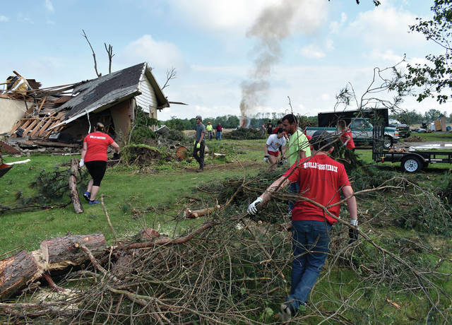 Dozens of Milton-Union students work to clean up the property of a Bulldogs supporter who lost his home to Monday's tornado.