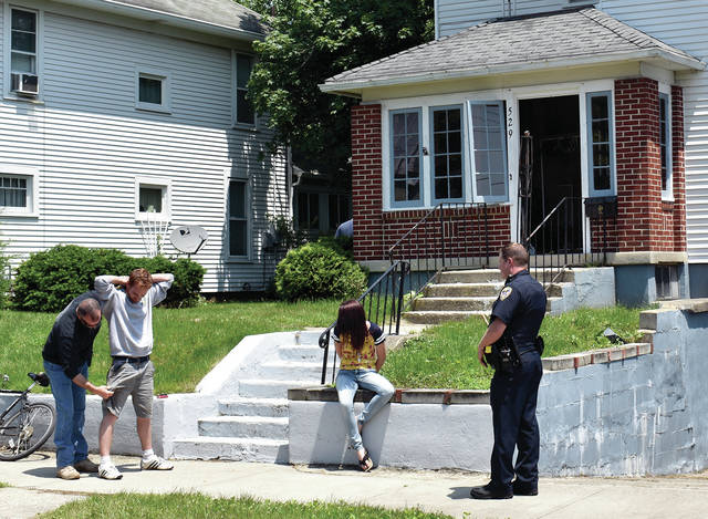 Troy Police Capt. Jeff Kunkleman pats down Travis Wilt, 33, of Troy, as Sgt. Matt Collett keeps an eye on Christina Meyers, age and address unknown, outside a home in the 500 block of Pennsylvania Avenue on Monday afternoon. The subjects were two of seven arrested following a reported overdose at the home. The home was supposed to be vacant. Troy P.D. has responded to the residence 27 times since Jan. 1. ©2019 Miami Valley Today. All rights reserved